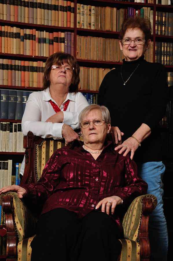 three senior ladies in front of a bookshelf - family