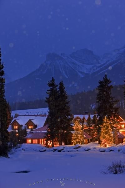 This wintry snow covered night scene that is illuminated and surrounded by trees and decorated trees is the Post Hotel located on the banks of the Pipestone River in Banff National Park in the Canadian Rocky Mountains, Alberta.