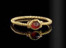 A gold ring with a gemstone garnet, Roman, 3rd century A.D.