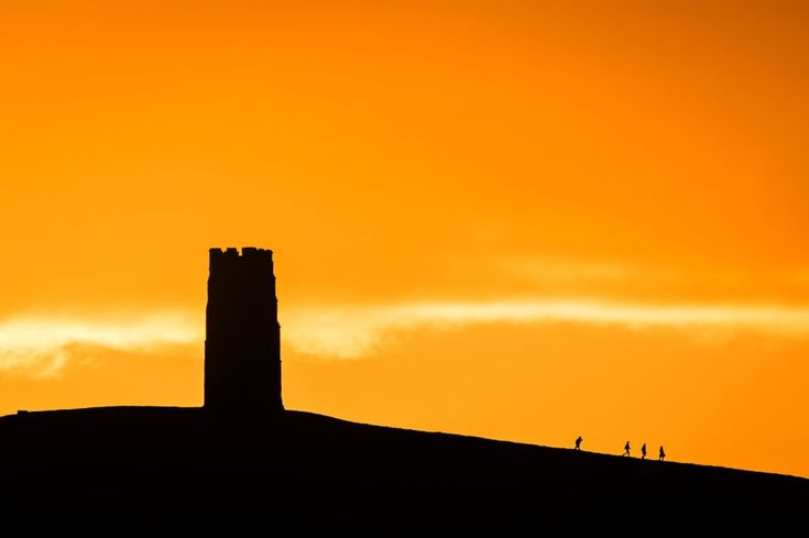 """26 November, Glastonbury: People trek from St Michael's Tower after watching the sun rise over Glastonbury Tor, Somerset, after forecasters issued a yellow """"be aware"""" weather warning for the length of the western side of Britain."""