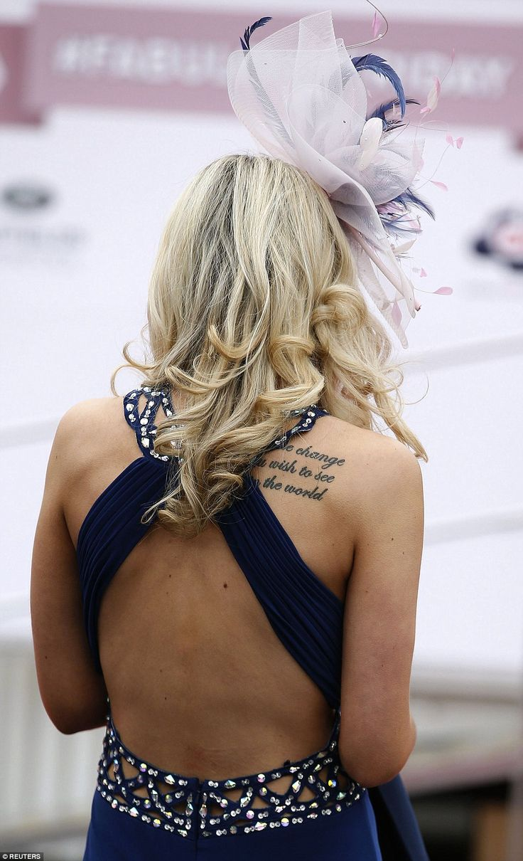 A woman displays her tattoo of Mahatma Gandhi's famous words: 'Be the change you wish to s...