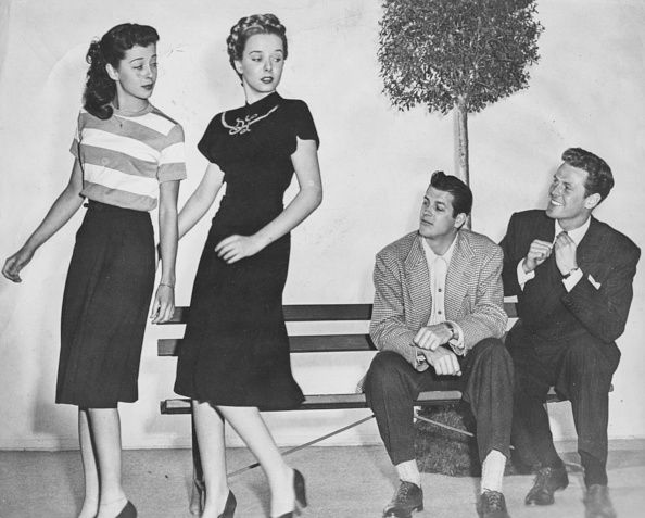 Actors James Brown and Bill Edwards sitting on a park bench watching actresses Gail Russell and Diana Lynn walk past as they appear in the film 'Our...