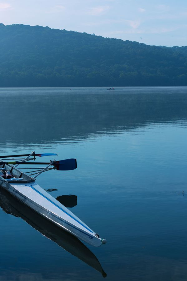 Scull boat docked on lake in morning light in front of green hills in summertime. #scullboat #lake #outdooractivity #rowing #lifestyle #watersport #water This image and many others are available for sale thru my website.