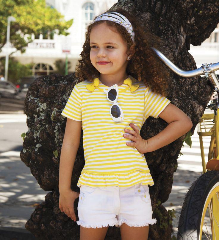 El turno ahora es para las niñas, proponemos una camisa a rayas blancas y amarillo carioca con un short denim blanco, para que se sienta cómoda y fresca en esta tarde de primavera.