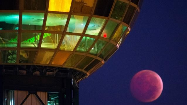 Professional photographers around the world also took pictures of the rare event, including this image of the blood moon in October 2014 next to the Sunsphere in Knoxville, Tennessee. (AAP)
