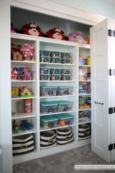 A beautifully organised toy cupboard in a play room using clear storage tubs with labels to organise and categorize the different toy collections, and large fabric baskets for the bigger toys. Organisation heaven!