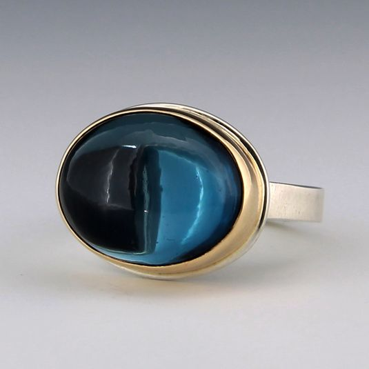 """London blue topaz is sought after for its deep vibrant color, and this Jamie Joseph ring features a beautiful specimen. The oval cabochon topaz is set in a 14k yellow gold bezel and sits on a sterling silver """"X"""" band.Stone measures 1/2"""" x 3/4"""".Size 5.75.Special Sizing:There is no charge for a first time sizing.Delivery for a special sizing is 4 weeks.Please contact us below for a special sizing request."""