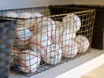 Wire baskets are a terrific way to organize shelves, providing rustic storage for displaying baseballs and sports equipment.