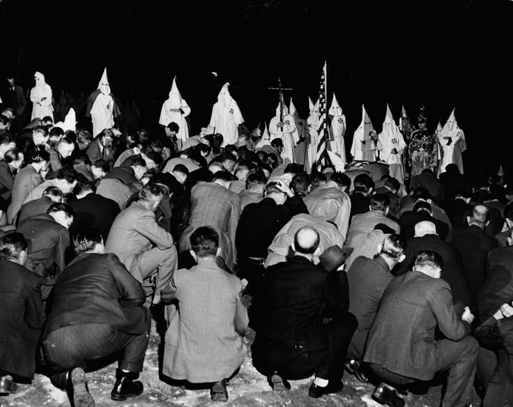 The new members of the Ku Klux Klan, including some Atlanta police officers, kneel in front of the Grand Dragon of the region, 1946  Photo credit: Life Magazine — in Atlanta, Georgia.