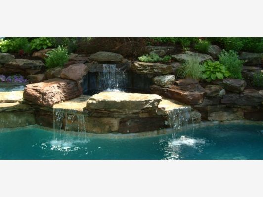 Beautiful stone waterfall into a pool home and garden for Beautiful swimming pools with waterfalls