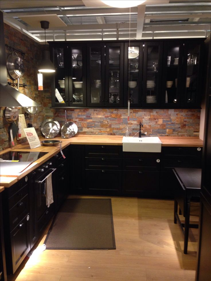Black caninets, white farmhouse sink, butcher block countertops.