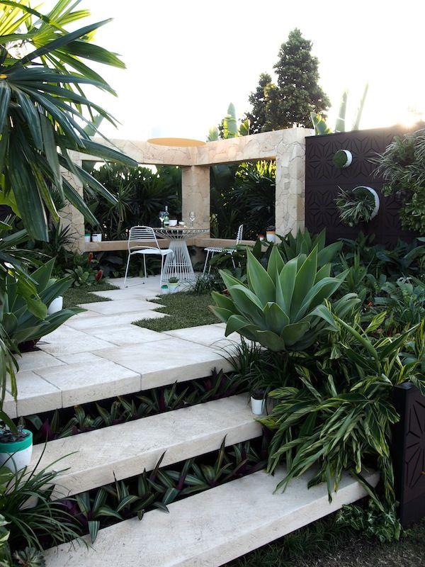 Terraza despues de los arboles con palmas en el límite de propiedad para dar fondo verde...escalones con peraltes verdes...