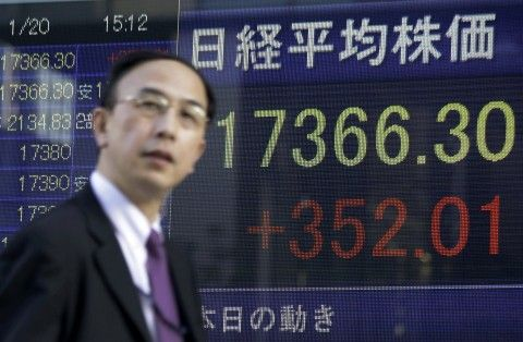 A man walks past an electronic stock board of a securities firm in Tokyo, Tuesday, Jan. 20, 2015. Asian stock markets rose Tuesday, and Shanghai rebounded from a dramatic dive the day before, after China's economic slowdown in the fourth quarter wasn't as sharp as feared. (AP Photo/Eugene Hoshiko)