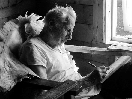 Arne Naess  working in his hut