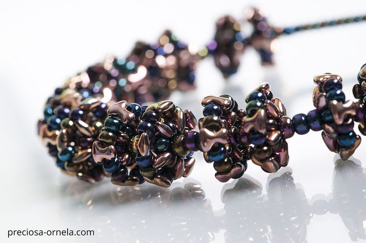 "Design: Karolina Emingrova PRECIOSA ORNELA presents the new PRECIOSA Tee™ pressed bead from the PRECIOSA Traditional Czech Beads™ brand. Its dimensions of 2 x 8 mm conform to the current trend in mini-beads. The axially symmetrical flat shape of the letter ""T"" enables the application of vacuum half-coatings on both sides of the bead with the resulting effect of an allover coating and other popular surface coatings. The strung beads closely interlock and create an interesting zip effect. It…"