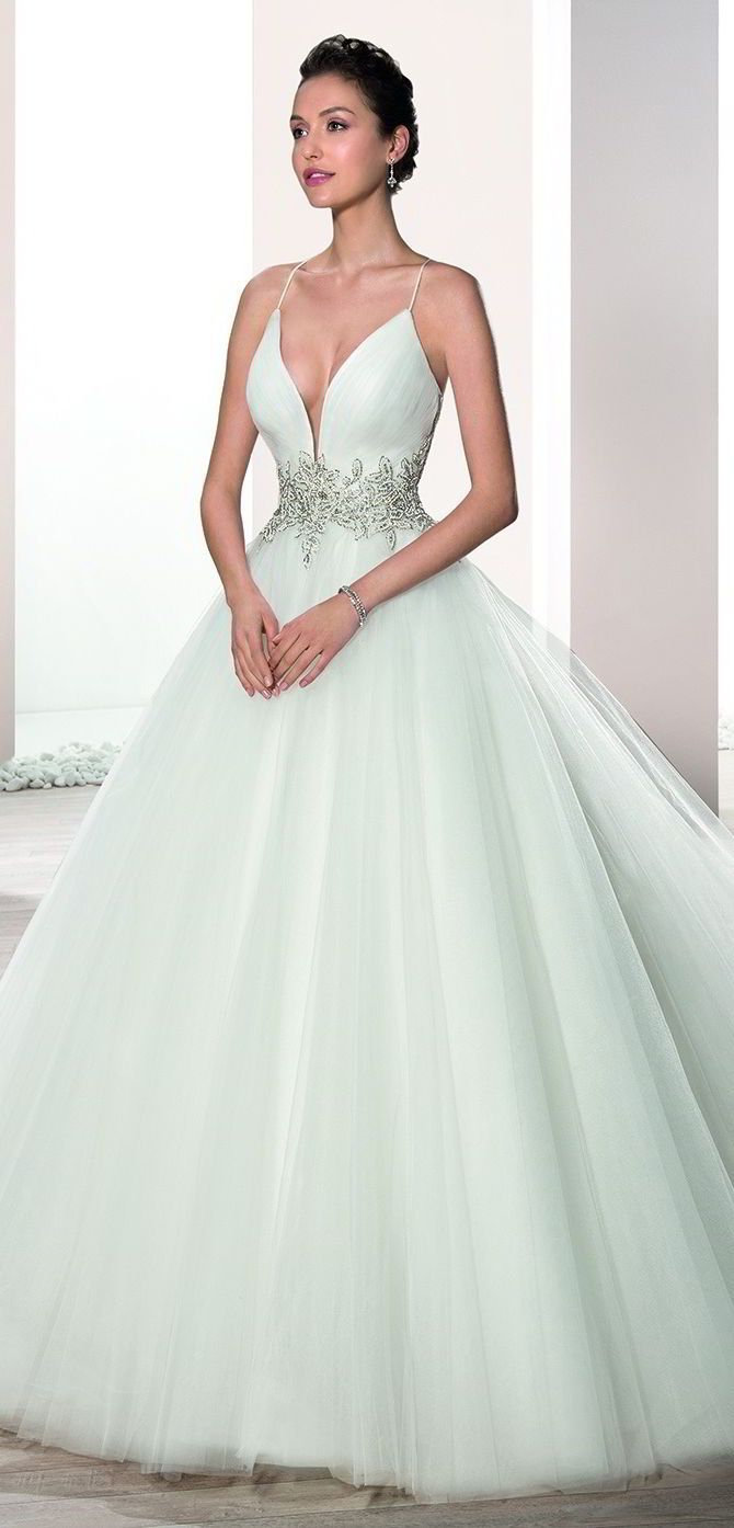 This striking Tulle Ball gown with spaghetti straps and plunging V-neckline is embellished with sparkling beaded embroidery on the waist and features a Chapel length train.