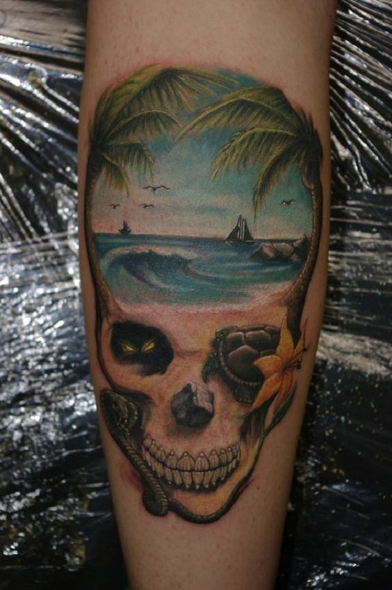 A beach tattoo framed by a skull like projection. Parts of the beach are arranged to form a skull enclosing a shore and the waters. It's both artistic and very creative in design.