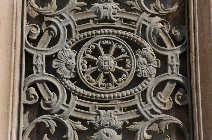 Большая старинная двустворчатая дверь с украшениями из железа.