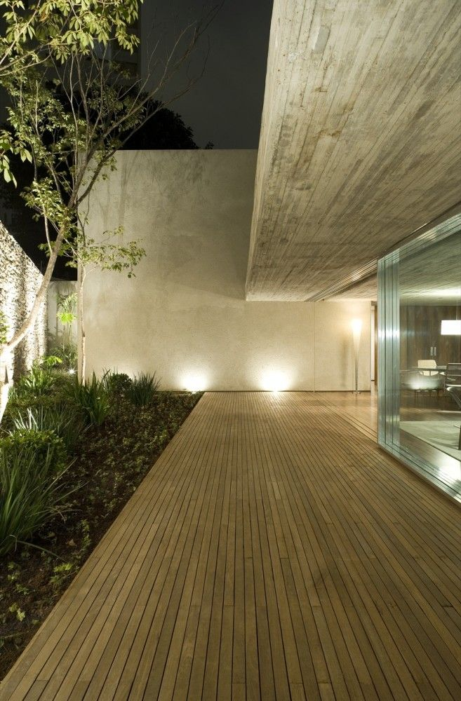 The wood deck is reflected in the narrow wood-formed concrete ceiling.