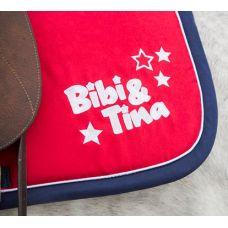 Leuk Zadeldekje van Bibi en Tina, bekend van de uit duitsland afkomstige serie die gaat over deze twee hartsvriendinnen. In de buurt van hun manege beleven ze vele advonturen op hun paarden. Speciaal van hun is er nu dit zadeldekje dat gevoerd is met een dikke vulling (schuim) en gewatteerd is. Natuurlijk voorzien van het B&T logo.