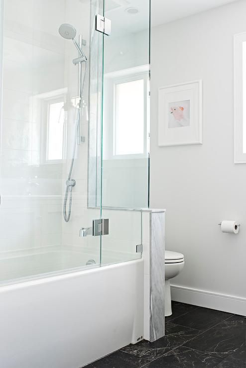Honed black marble floor tiles frame a white drop-in bathtub enclosed behind a seamless glass enclosure and fitted with an exposed plumbing polished nickel shower kit and tub filler.