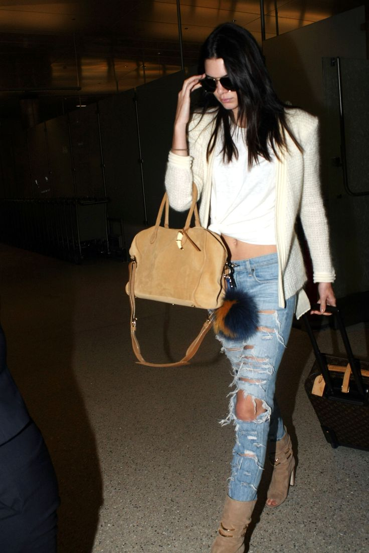 Kendall Jenner steps out in Los Angeles wearing a sweater, ripped jeans, and a white knotted t-shirt.