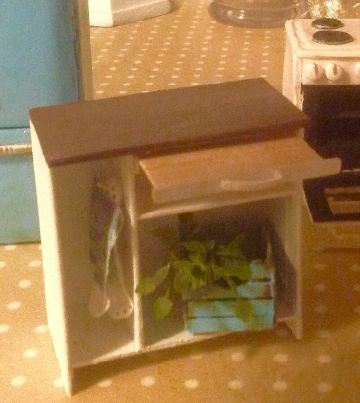 A tiny 1:12  for the dollhouse kitchen. I made this one from cardboard for the countertop, popsicle stics for the cuttingboard and framing, an skinnysticks for holding the shelves