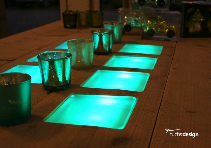 Beleuchtete Glassteine treffen Bauholztisch