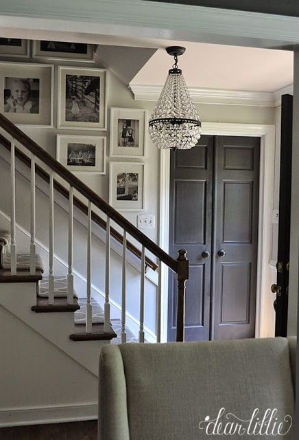 black doors, black and white wall gallery, wood + white, grey + white, stair runner, entrance chandelier