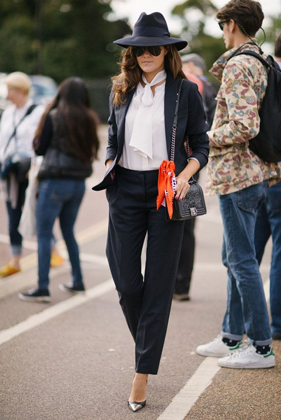 spring work outfits - 30 Spring Work Outfits To Try Right Now: Fashion Blogger 'The Londoner' wearing a navy wide brim fedora, a navy blazer, a white tie neck blouse, navy ankle pants, navy metal cap pointy toe heels, aviator sunglasses, a black shoulder bag and an orange bandana.