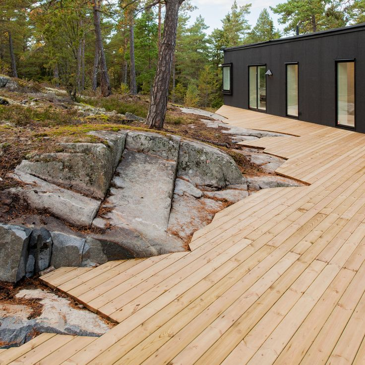 Villa Blåbär by pS Arkitektur. The surrounding nature and slope dictated the shape of this house fully covered in black roofing felt, and features the beautifully crafted timber deck.