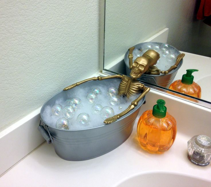 My version of the dollar store skeleton taking a bath bathroom decoration. $1 skelleton from dollar store, $1 tub/bucket from Target, $3 batting for stuffed animals, $3 ornaments from Hobby Lobby.