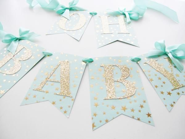 "- Mint medium weight cardstock - Star pattern - Gold foil vellum overlay - Gold glitter letters - 3 inches tall - Mint satin ribbon - ""OH"" spans 9 inches from bow to bow, ""BABY"" spans about 18 inches"