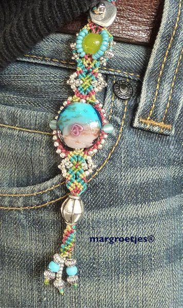Een unieke tassenhanger, die ook mooi aan een jeans staat!Geknoopt volgens de nomadknots en volgens Cavandoli knots in een enkele kleur of in meerdere kleuren.Met veel zilverkleurige kraaltjes, Tibetaans zilver, metalen kralen,parels , glazen kralen, versierseltjes.Vrolijk voor in de lente, in de zomer aan een lusje van een broek. In de herfst ...