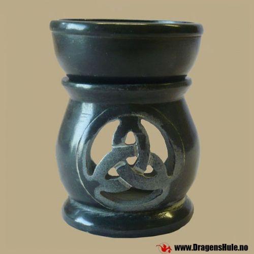 En fin duftoljevarmer i to deler, håndlaget i svart klebersten med gjennomboret triqueta foran og åpning bak. Fordi det er håndlaget, er hver unikt og litt forskjellig fra det forrige.  Materiale: Svartmalt klebersten. Mål: ca 9 cm høy. Sokkelen er ca 6 i diameter. Passer til et typisk te-lys. Den løse skålen er ca 6,5cm i diameter.