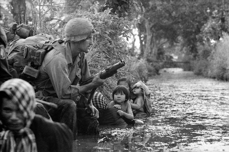 Dos niños survietnamitas abrazados a su madre observan a un paracaidista estadounidense con un lanzagranadas M79, mientras buscan refugio de los francotiradores del Viet Cong, en la zona de Bao Trai a 32 km al oeste de Saigón