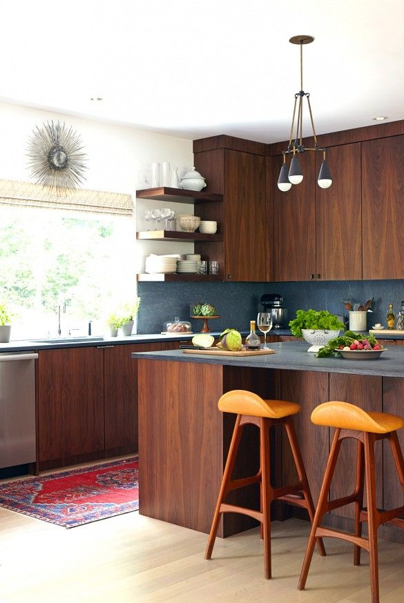 Counters of slate are brought up the walls as a backsplash in the  midcentury-inspired kitchen.