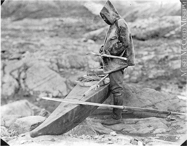 MP-0000.597.166 | Homme près d'un kayak avec du matériel de chasse, dont un harpon, vers 1919