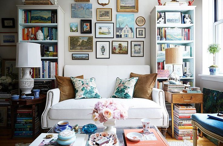 The white sofa perfectly anchors the colorful accents and bookshelves surrounding.
