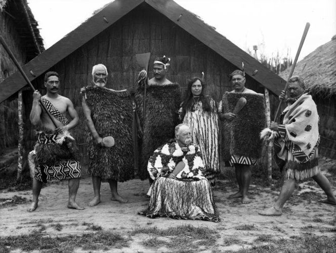 Group outside a whare at the New Zealand International Exhibition in Christchurch