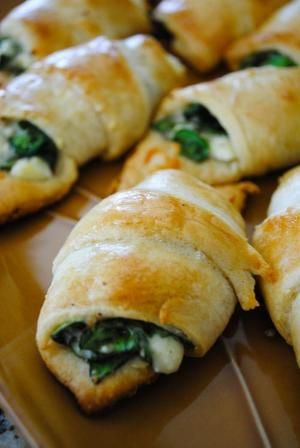 Cheesy Spinach Crescent Rolls  2 tubes crescent rolls  Pillsbury (8 ct. each) 4 oz. crumbled feta cheese 4 oz. shredded mozzarella cheese 3 oz. fresh baby spinach  chopped (about half of a pre-washed bag) 1 egg white  beaten 1/4 tsp. red pepper flakes dash of salt and pepper. by jill