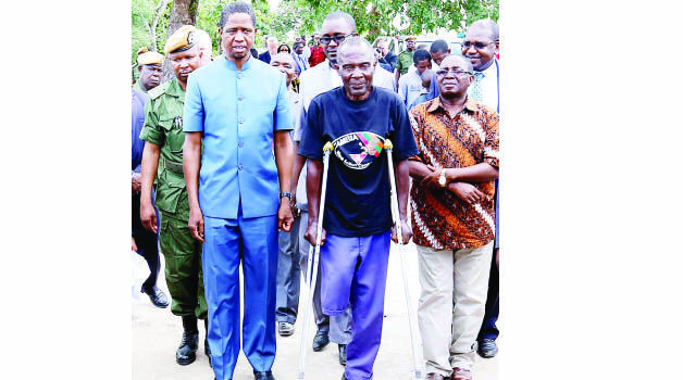 • President Edgar Lungu walking with a landmine victim inIkeleng'i yesterday. Right is Foreign Affairs deputy minister Rayford Mbulu. Picture by EDDIE MWANALEZA/STATEHOUSE.