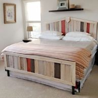 Using the planks of discarded pallets, old boards from his neighbor's deck, and a cheap metal bed, this handy homeowner made his wife a lovely bed for their 14th wedding anniversary.