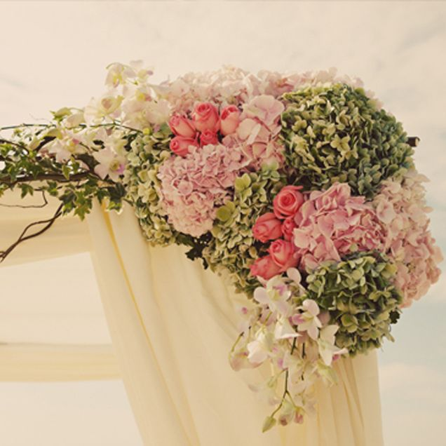 Pastel flowers decorate the ceremony canopy.