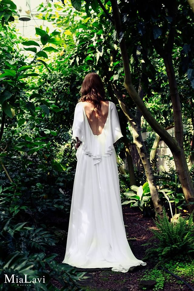 MODEL 1716 Romantyczna, zwiewna suknia ślubna. Góra sukni koronkowa ze zwiewnymi szerokimi szyfonowymi rękawami, które są przedłużone na tyle. Plecy mocno wycięte do linii talii. Spódnica obszerna, wykonana z szyfonu z trenem. Całość dopełnia zdobny koralikowy pasek.