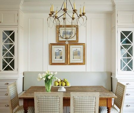 Paint the interiors of glass-fronted cabinets for a hint of colour that can easily be changed. A classic symmetrical design ~The distressed table and gingham-upholstered antique chairs add rustic charm, while drawers beneath the banquette make full use of space.