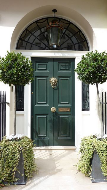 Emerald green front door with symmetrical potted topiary boxwoods.