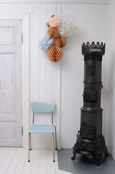 homes - norway house: white wall with pastel chair and cast iron oven