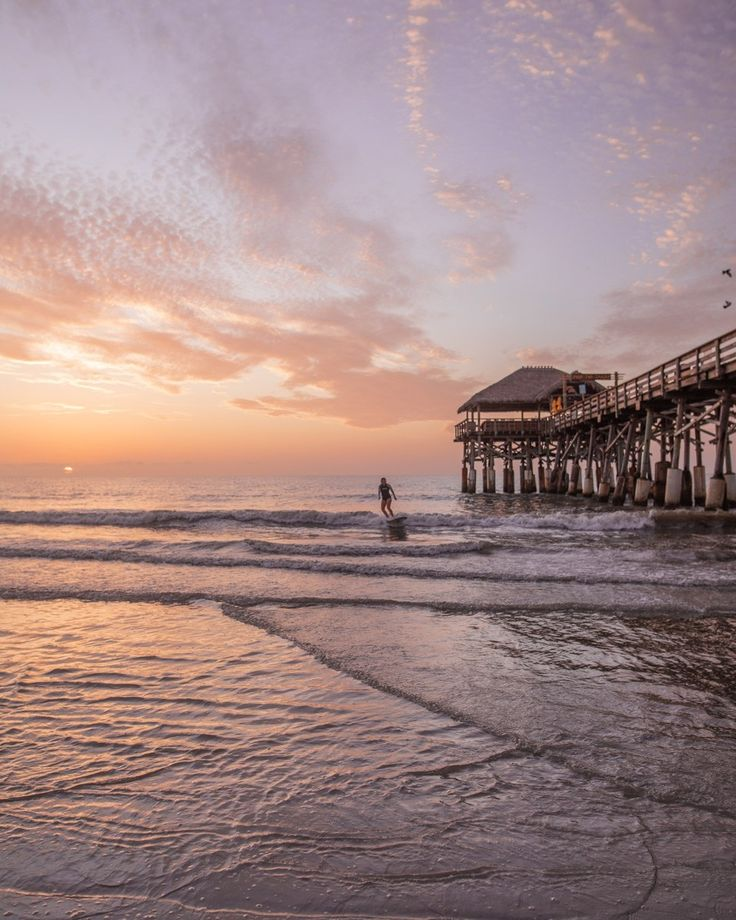 A female surfer catches a wave next to the Westgate Cocoa Beach Pier. Find out everything you need to know for the perfect Florida beach vacation here.