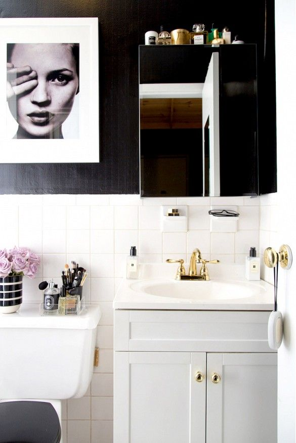 We can't get enough of this dramatic black and white bathroom makeover. Bold black walls have a striking effect against white tiles. Gold hardware finishes this edgy look.